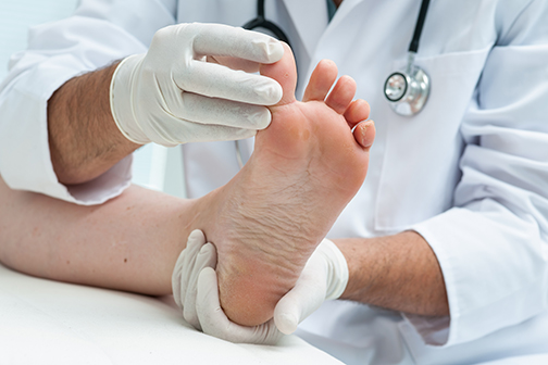 photo of a podiatrist examining a big toe   American Foot & Leg Specialists