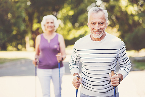 photo of a handsome senior man smiling while walking in the park with a woman walking behind him